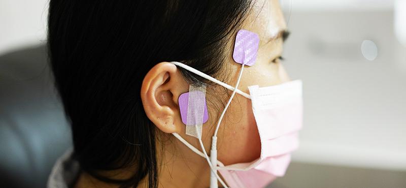 物理治療師在醫師開立的體表神經點位置貼上貼片